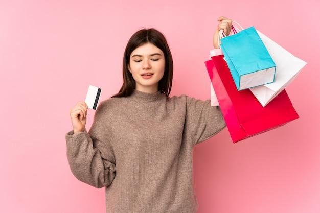 ショッピングバッグとクレジットカードを保持しているピンクの壁の上の若い10代の女の子