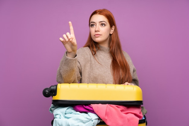 透明な画面に触れる服でいっぱいのスーツケースを持つ旅行者10代の女の子