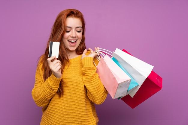 ショッピングバッグとクレジットカードを保持している分離の紫色の壁の上の赤毛の10代女性