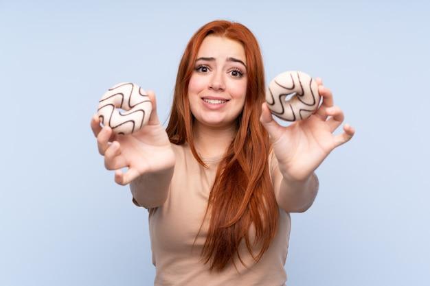 ドーナツと悲しいを保持している赤毛の10代女性