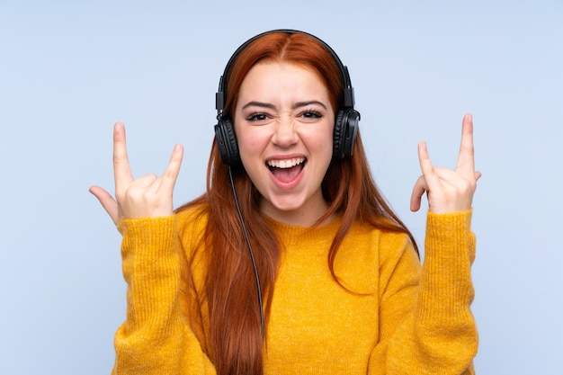 ロックジェスチャーを作る音楽を聞いて赤毛の10代女性