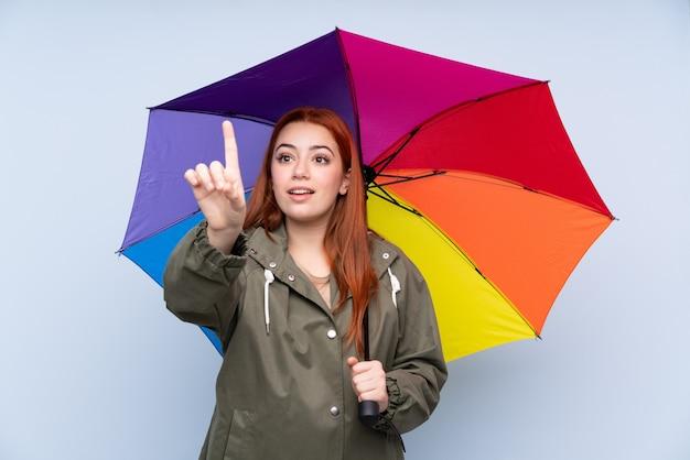 透明なスクリーンに触れる傘を保持している赤毛の10代女性