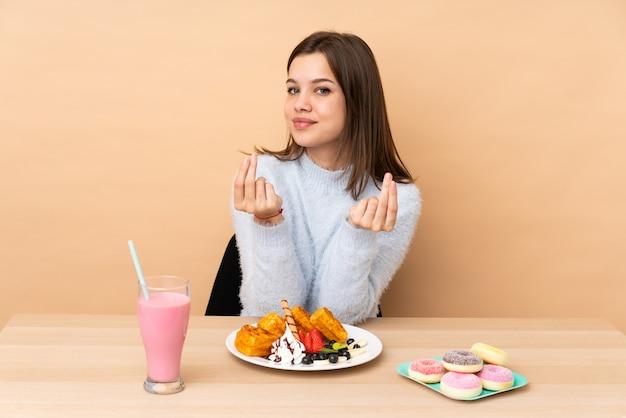 お金のジェスチャーを作るベージュのワッフルを食べる10代の女の子