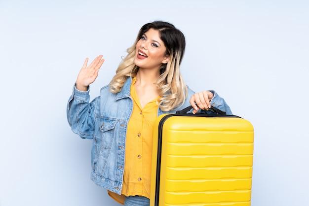 旅行スーツケースと敬礼と休暇で青い壁にスーツケースを保持している旅行者10代