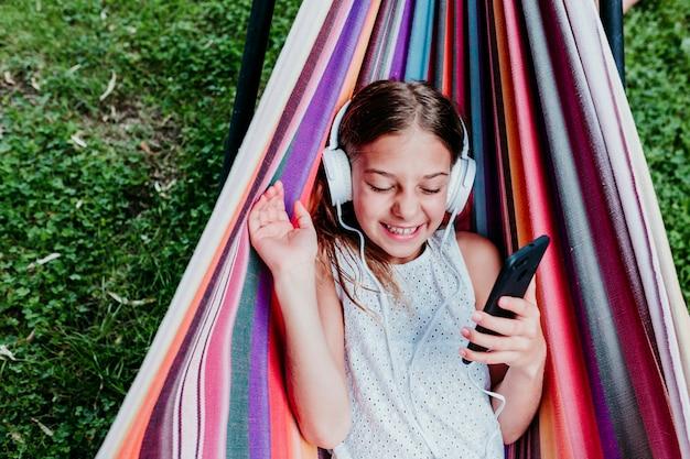 庭でカラフルなハンモックに横たわっている美しい10代の女の子。携帯電話とヘッドセットで音楽を聴いて笑顔