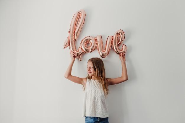 自宅で愛の形をしたピンクの風船を保持している陽気なかわいい10代の女の子の肖像画。幸福とライフスタイルのコンセプト