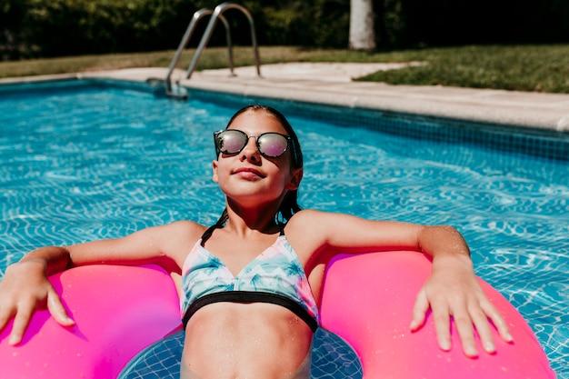 プールでピンクのドーナツに浮かぶ美しい10代の女の子。サングラスをかけ、笑顔。楽しさと夏のライフスタイル