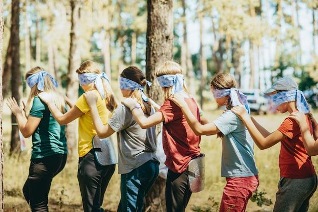 10代の若者は隣同士に立って、近くに立っている人の肩に手を置きます。目は全然目隠し。チームビルディング演習、チーム精神。チームの関係を強化する。