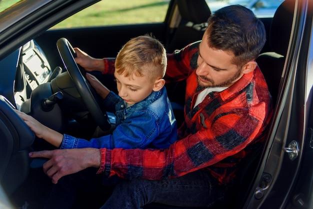 車を運転する10代の息子を教えている間何かを指しているハンサムな父親