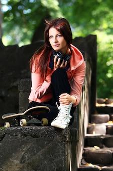 公園でヘッドフォンで美しい10代の女の子