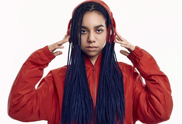 音楽を聴く赤いウインドブレーカーでドレッドヘアを持つアフリカの10代の少女