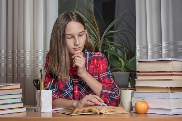 10代の少女は彼女の宿題をやっています。