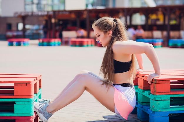 ストリートの壁、アウトドアスポーツ、都会的なスタイルでファッションスポーツウェアを着てフィットネススポーティな女の子。外でポーズ盗品服で10代のモデル