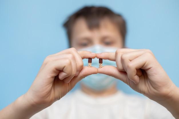 防護マスクで10代の少年は、手で薬のカプセルを保持しています。コロナウイルスの患者の中で、ウイルスから保護されたインフルエンザの子供