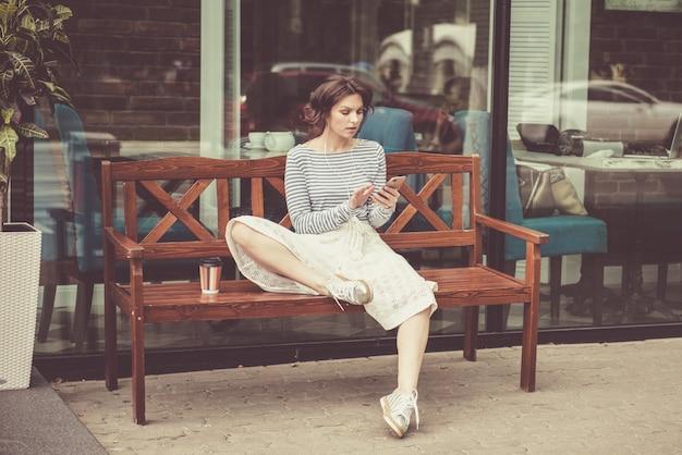 スマートフォンとヘッドフォンが音楽を聴く、ベンチに座ってかわいい流行に敏感な白人の10代の少女。現代の若者のライフスタイル