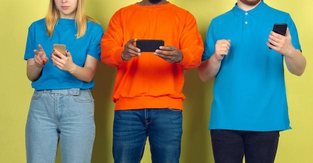 モバイルスマートフォンを使用している友人のグループ。 10代の若者が新しいテクノロジーのトレンドに依存している。閉じる。