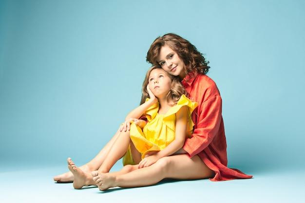 10代の娘と妊娠中の母親。青い背景上の家族のスタジオポートレート