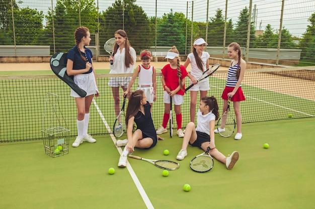 屋外コートの緑の芝生に対してテニスラケットを保持しているテニス選手としての女の子のグループの肖像画。スタイリッシュな若い十代の若者たちが公園でポーズします。スポーツスタイル。 10代と子供たちのファッションのコンセプト。