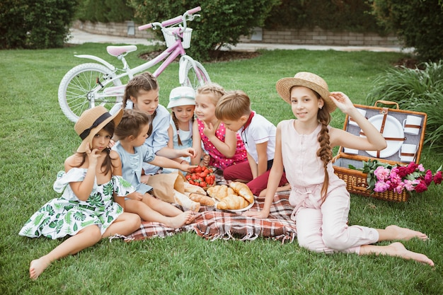子供のファッションのコンセプトです。公園で緑の芝生に座っている10代の男の子と女の子のグループ。