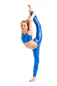 白い背景で隔離の体操の練習をしている10代の女の子