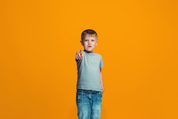 あなたを指している幸せな10代の少年、オレンジ色のスペースの半分の長さのクローズアップの肖像画。