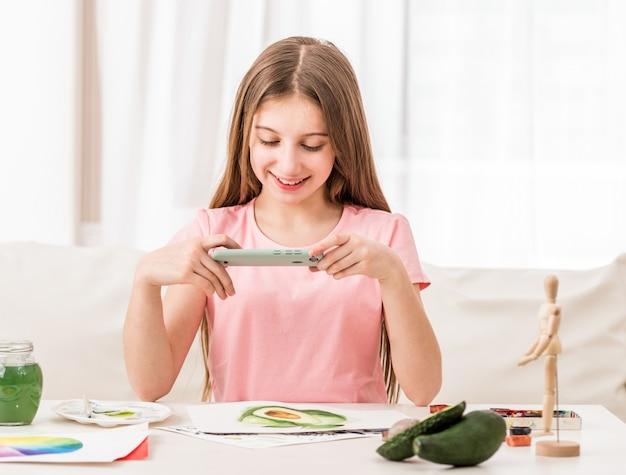 彼女の新しい絵画の写真を撮る10代の女性