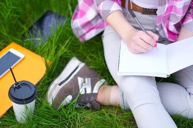 10代の少女学生が公園でノートに書きます。大学での試験準備