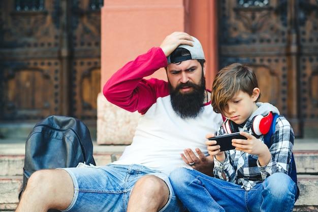父と息子はスマートフォンを使用しています。お父さんと息子が屋外で一緒に時間を過ごします。電話でゲームをプレイ10代の少年。