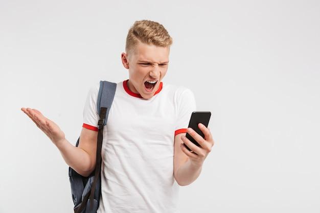 バックパックで立っている怒っている10代の少年のポートレート