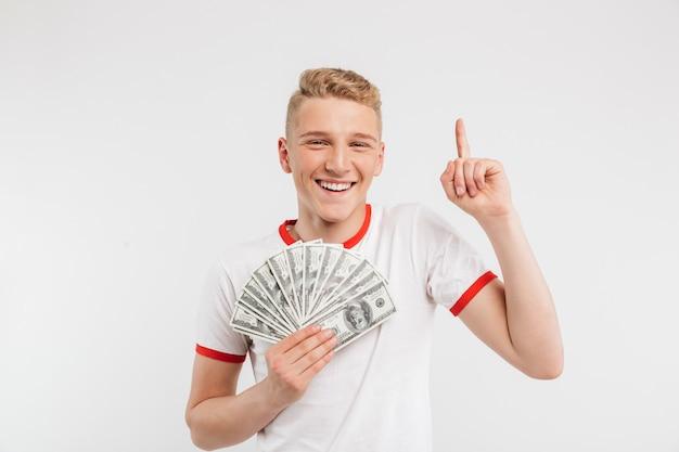 お金紙幣を保持している笑顔の10代の少年のポートレート