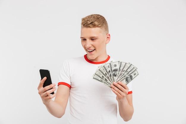 お金紙幣を保持している幸せな10代の少年のポートレート