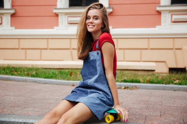 スケートボードの上に座って笑顔の若い10代の少女