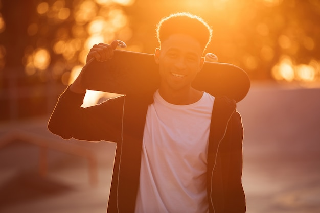 肩にスケートボードを持って笑顔の男性10代の男