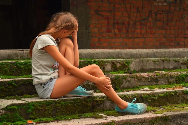 外の古いコンクリートの上に座っている気分を害した動揺の女の子10代