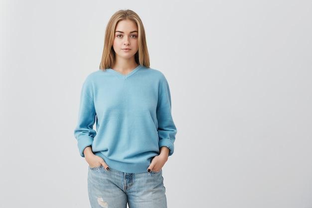 深刻なまたは物思いに沈んだ表情で見ている青いトップを着て健康な肌を持つ若い優しい公正な髪の10代の少女。屋内でポーズのポケットに手で白人女性モデル