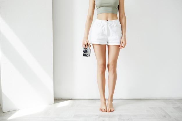 白い壁に古いカメラを保持している若い10代の女性の写真を閉じます。