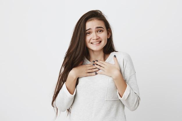 明るく暗いストレートの髪が元気に笑っている恥ずかしがり屋のかわいい10代の女性。前向きな感情、感情、顔の表情