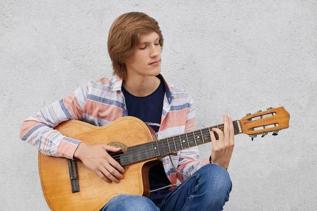灰色のコンクリートの壁に座っている間彼のお気に入りの曲を演奏するアコースティックギターを保持しているトレンディな髪型を持つ才能のある10代の少年