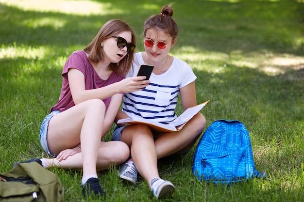楽しい探している10代の女性はスマートフォンを保持し、友人と一緒に画面を見て、緑の芝生で休んでいる間にオンラインショッピングをする