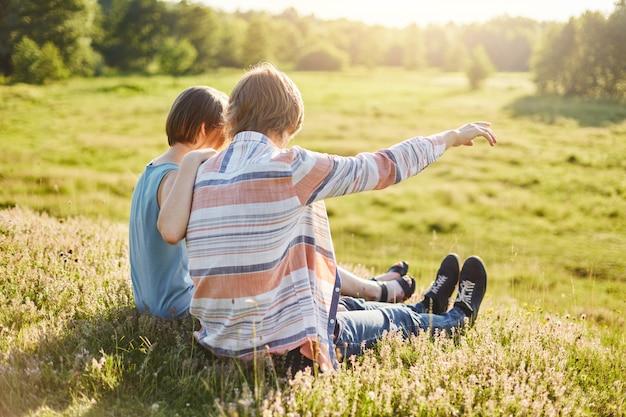 緑の野原に座って距離を指している彼のガールフレンドに手で何かを示す10代の少年。ロマンチックなガールフレンドとボーイフレンドは、屋外の夏休みを楽しみながら抱きしめる