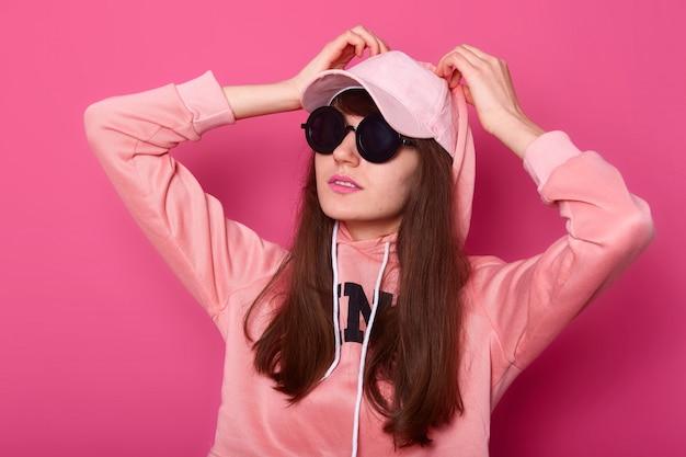 スタイリッシュなピンクのフーディ、キャップ、黒のサングラスのスタジオでポーズをとる若者のファッションモデルの10代の少女は、フードに手をつないでいます。