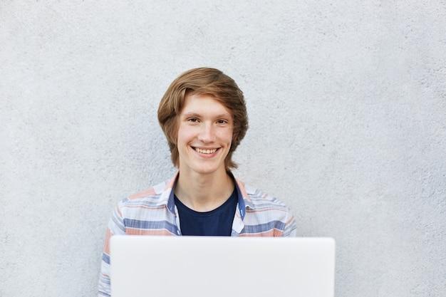 映画を見たりゲームをしたりするためにラップトップを使用して白い壁の上に座って魅力的な外観を持つ10代の少年の笑顔