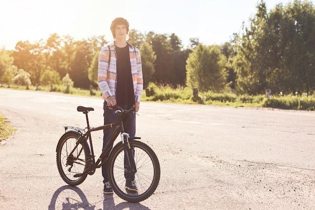 健康的なライフスタイルのコンセプトです。カジュアルなシャツ、ジーンズ、自転車で立っているスポーツシューズを着てトレンディな髪型を持つ10代の男性