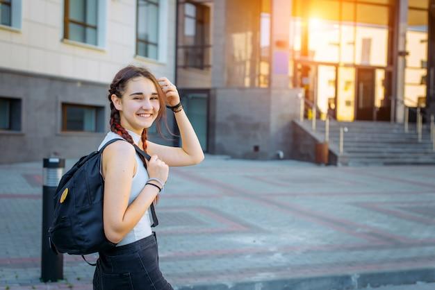 学校に戻る。バックパックで幸せな10代の少女の開いている肖像画