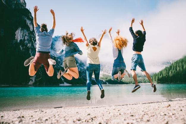 湖のビーチで過ごす10代の若者のグループ