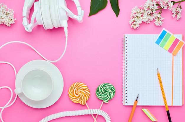 ピンクの背景の10代の子供のテーブル、ドリンクイヤホンロリポップとラップトップ消しゴムフラワーガラス用鉛筆の組成物の平面図