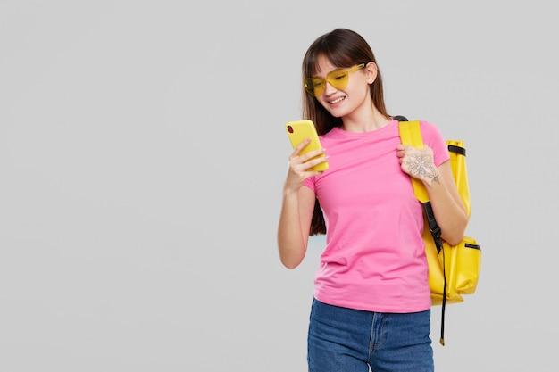 ハート型のメガネをかけたアジアの10代女性が携帯電話を手に持っています。新しいガジェット広告