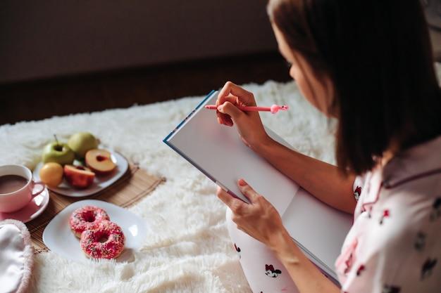 10代の少女は、ベッドで朝食をとりながら白紙に書き込みます。