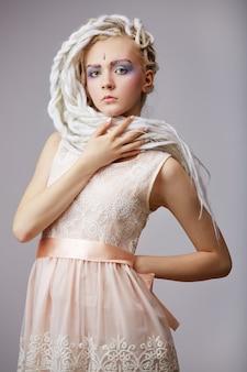 ドレッドヘアを持つ美しいブロンドの10代の少女