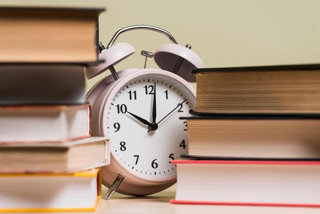 Будильник, показывающий время на 10 часов за книжной полкой